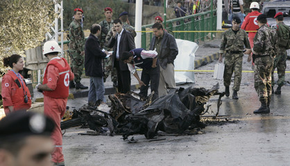 Security officials inspect the wreckage of a car at the site of an explosion in the Christian town of Baabda