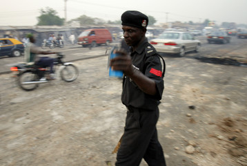 A policeman carries a tear gas canister on the outskirts of Kano