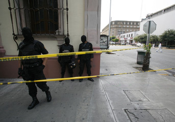 Hooded policemen stand guard next to a crime scene where Mexican state lawmaker Rios was gunned down in Monterrey