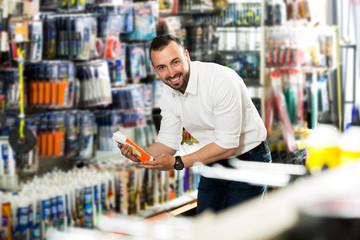 Man choosing sealant tube
