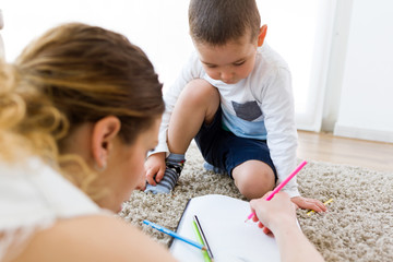 Beautiful young mother and her son drawing at home.