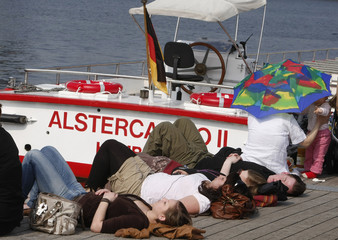 People enjoy sunny weather at Alster lake in Hamburg