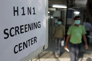 People wearing surgical masks walk out of a H1N1 flu screening centre in New Delhi