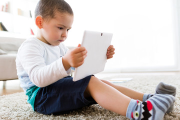 Beautiful young boy using his digital tablet at home.