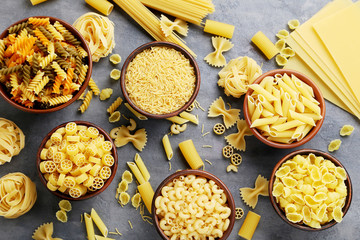 Different kinds of pasta in bowls on grey table