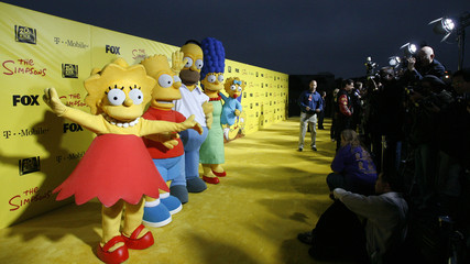 "Characters Lisa, Bart, Homer, Marge and Maggie stand by a cake at the 20th anniversary party for the television series ""The Simpsons"" in Santa Monica"