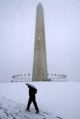 A visitor walks to the Washington Monument on the National Mall in Washington during snowfall