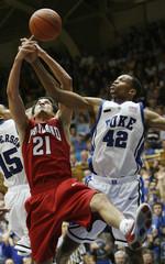 Duke University's Lance Thomas battles the University of Maryland's Greivis Vasquez for a rebound in Durham
