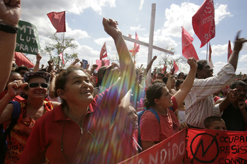 Squatters cheer during a speech by Roman Catholic priest James Crowe in the camp erected Brazil's Roofless Workers Movement in Itapecerica da Serra