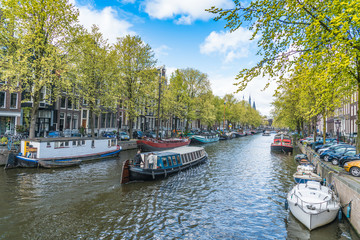 Amsterdam, The Netherlands, April 22, 2017: Local and tourist walking on the Keizersgracht Canal in spring in the Jordaan area with boats, bikes and cars