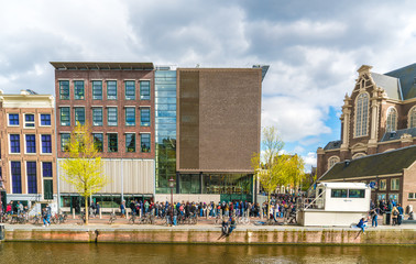 Amsterdam, The Netherlands, April 22, 2017: Tourists waiting in line to get in to the Anne Frank house in Amsterdam next to the Westertoren
