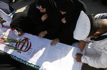 Iranian women and a pallbearer grieve on the coffin bearing the remains of Iranian soldier during a ceremony at the Iraq-Iran Shalamcha Border Crossing