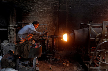 A laborer checks the heat of an oven while melting iron before pour into moulds to make machine parts in a foundry in Karachi,