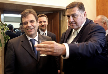 Serbian PM Kostunica is welcomed by Deputy Parliament Speaker Mrkonjic after the parliament approved his new government in Belgrade