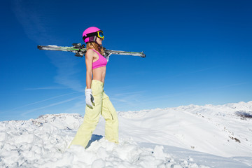 Female skier standing with skies on a snowy slope
