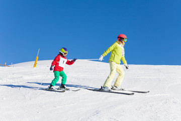 Sporty mother pulling her kid son on ski by a pole