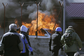 People walk away after Kosovo Serb protesters burned down Serbia Kosovo border crossing Jarinje