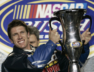 Driver Carl Edwards holds the NASCAR Busch Series championship trophy after the final race of the season, the Ford 300, at the Homestead-Miami Speedway in Homestead, Florida