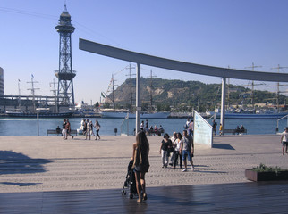 People walking on a sunny morning at Port Vell harbor in Barcelona