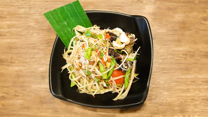 papaya salad with vermicelli and salted crab on black dish