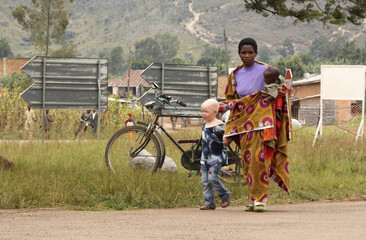 A woman walks with her albino son to courtroom in Ruyigi