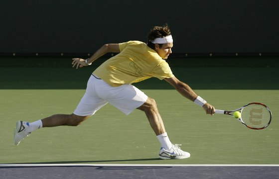 Switzerland's Roger Federer lunges to return the ball during a workout session at the Pacific Life Open tennis tournament in Indian Wells, California
