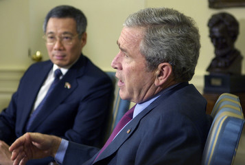 U.S. President George W. Bush (R) speaks to reporters with Singapore Prime Minister Lee Hsien Loong (L) in the Oval Office of the White House in Washington