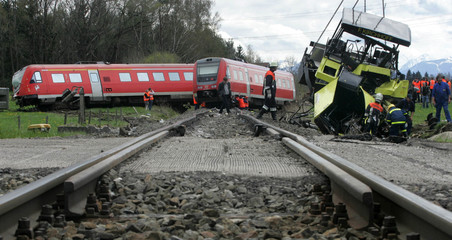 Rescue workers examine the spot of a derailed train after a crash with a construction vehicle in ...