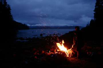 A man stands next to a bonfire on the shore of Nahuel Huapi lake in Argentina's Patagonian city of Bariloche