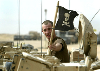 US INFANTRY SOLDIER ADJUSTS A SKULL AND CROSSBONES ON TOP OF HISARMOURED VEHICLE AT CAMP VIRGINIA ...