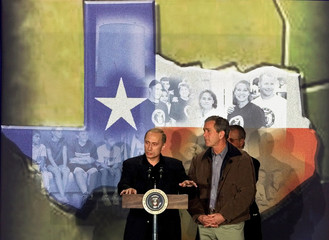 With a mural of the state of Texas in the background, U.S. President George W. Bush (R) looks on as ..