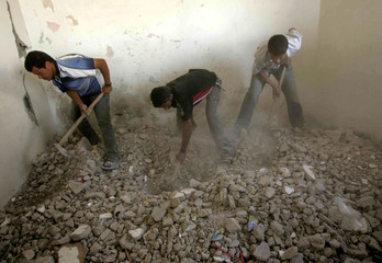 Palestinians search through the rubble for bodies after an explosion ripped through a house in the southern Gaza Strip