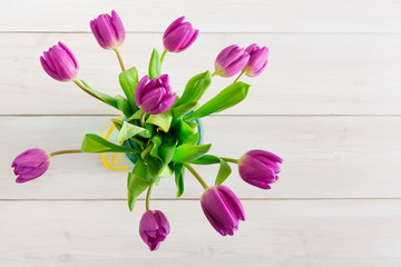 Violet tulips bouquet on white wood background, top view