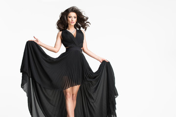 Sexy brunette woman in long black dress over white background