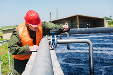 An engineer controlling a quality of water ,aerated activated sludge tank at a waste water treatment plant