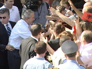 A television grab shows U.S. President George W. Bush wearing his wristwatch as he shakes hands with Albanians in Fushe Kruje