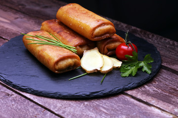 Crispy golden fried spring rolls with fresh ingredients served in an oriental restaurant