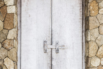 Wooden textured white door with latch, rustic interior in Bali house