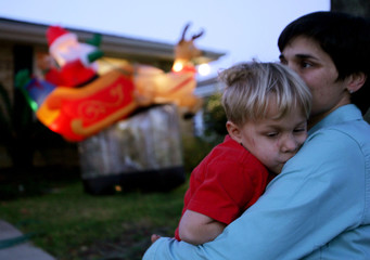 Woman holds her son in front of a blow-up Santa Claus doll in New Orleans