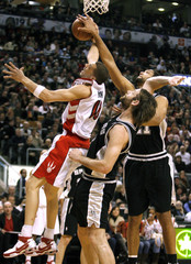 Toronto Raptors forward Anthony Parker has a shot blocked by San Antonio Spurs Tim Duncan and Fabricio Oberto in Toronto