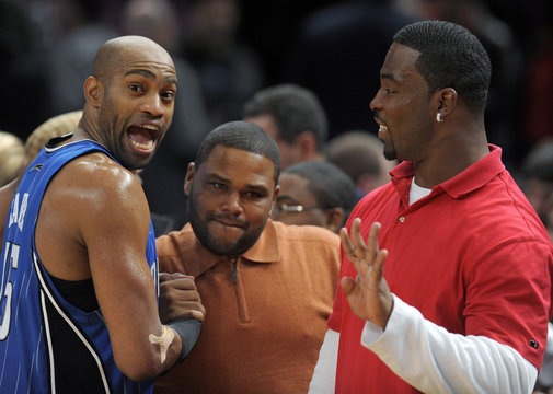 Orlando Magic guard Carter reacts as he shakes hands with actor Anderson and New York Giants player Tuck after their win over the New York Knicks in their NBA basketball game in New York