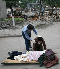 A policeman comforts man mourning in front of body of father following Monday's earthquake in Hanwang