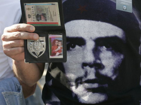 A policeman displays his police badge and identity card during a demonstration in Lisbon