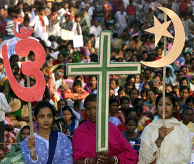 Indian Christian women hold symbols (from L to R) of Hinduism, Christianity and Islam during a Human..