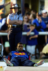 AMERICAN LONG JUMPER STRINGFELLOW RELAXES UNDER THE WATCFUL EYE OF THE POLICE.