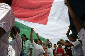 Palestinians hold large Palestinian flag during rally against barrier in Beit Jala