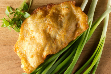 Fried cheburek with meat with green onions and Basil on wooden background