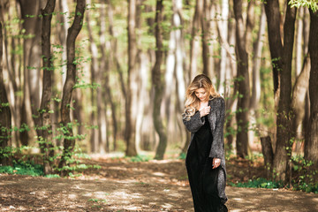 Stunning young lady in grey coat and black dress poses in the forest