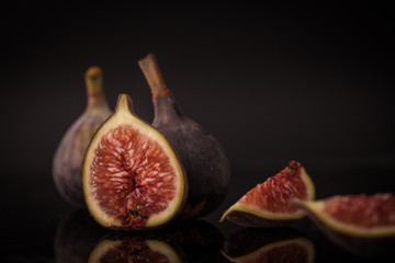 Figs on a reflective black surface