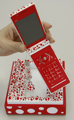 Japanese mobile phone carrier KDDI's new mobile phone and a box designed by Japanese artist Yayoi Kusama is displayed in Tokyo